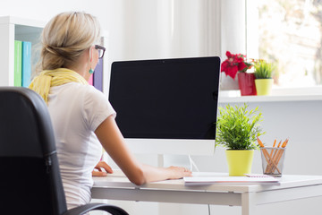 Young creative woman working with computer in the office