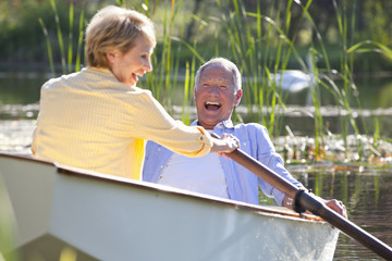 Smiling couple in rowboat on lake