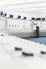 Engineer with binder at control panel in control room of nuclear power station