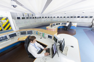 Engineers at computers in control room of nuclear power station