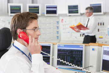 Engineer on telephone at computers in control room of nuclear power station