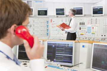 Engineers in control room of nuclear power station