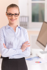 Modern business woman standing in office.