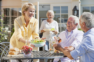 Smiling senior couples drinking wine and enjoying lunch on sunny patio
