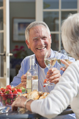 Smiling senior couple drinking wine and enjoying lunch on sunny patio
