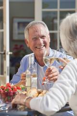 Smiling senior couple drinking wine and enjoying lunch on sunny patio