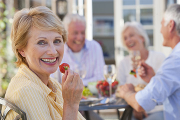 Portrait of smiling senior woman eating strawberry on patio with friends enjoying wine and lunch in background