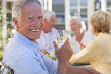 Portrait of smiling senior man drinking white wine on patio with friends in background