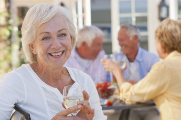 Portrait of smiling senior woman drinking white wine on patio with friends in background