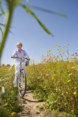 Happy senior woman riding bicycle on path in sunny wildflower meadow