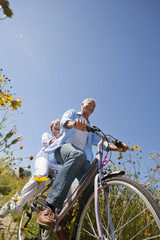 Happy senior couple riding bicycle on path in sunny wildflower meadow