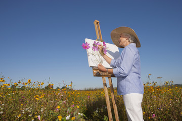 Senior woman painting in sunny wildflower field