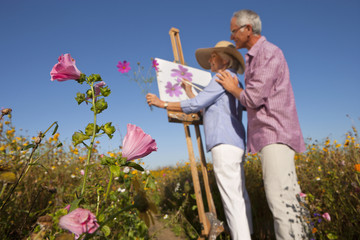 Senior couple painting in sunny wildflower field