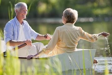 Smiling senior couple in rowboat on sunny lake