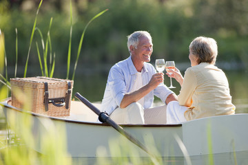 Smiling senior couple drinking wine in rowboat on sunny lake