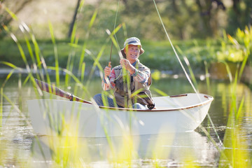 Smiling senior man fishing in rowboat on sunny lake