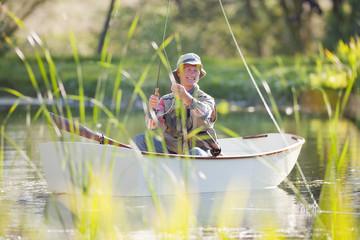 Smiling senior man fishing in rowboat on sunny lake