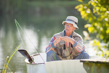 Senior man preparing fishing rod in rowboat on sunny lake