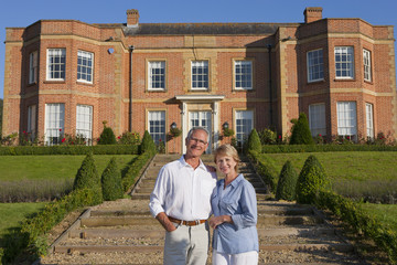 Portrait of smiling couple in front of luxury estate