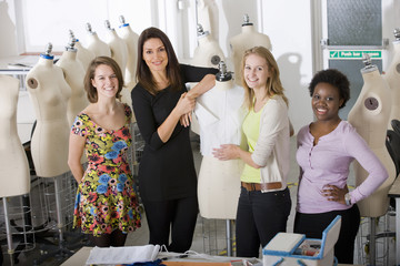 Fashion design students with lecturer in university classroom