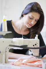 Seamstress using industrial sewing machine