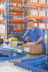 Portrait of smiling worker scanning cardboard box on production line in distribution warehouse