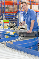 Portrait of smiling worker with bin on production line in distribution warehouse