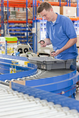 Worker examining machine parts in bin on production line in distribution warehouse