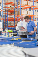 Supervisor and worker examining machine parts in bin on production line in distribution warehouse