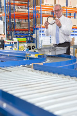 Supervisor examining machine part in bin on production line in distribution warehouse