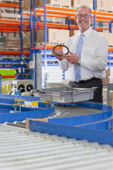 Portrait of smiling supervisor examining machine part in bin on production line in distribution warehouse
