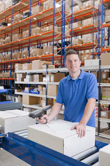 Portrait of smiling worker scanning box on production line in distribution warehouse