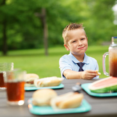 little boy at picnic table eating food
