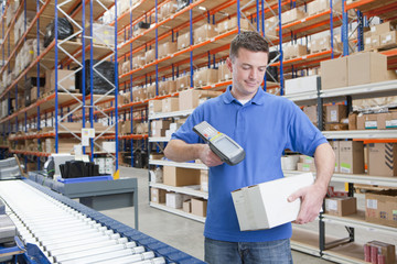 Worker scanning box at production line in distribution warehouse