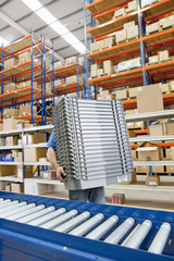Worker carrying stack of bins in distribution warehouse
