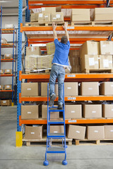 Worker on ladder reaching for cardboard box on shelf overhead in distribution warehouse