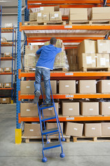 Ladder tilting under worker reaching for cardboard box in distribution warehouse