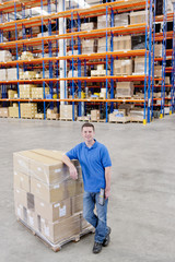 Portrait of smiling worker leaning on pallet of cardboard boxes in distribution warehouse
