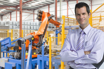 Portrait of smiling businessman near robotic machinery in factory