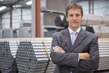 Portrait of confident businessman leaning on stacked steel bundles in warehouse