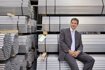 Portrait of confident businessman sitting on stacked steel bundles in warehouse