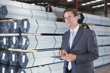 Businessman using digital tablet in front of steel tubing in warehouse