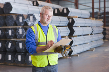 Worker writing on clipboard in front of steel tubing in warehouse