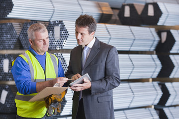 Businessman and worker with clipboard and digital tablet in front of steel tubing