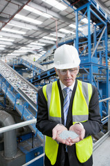 Businessman examining plastic pellets in recycling plant