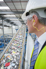 Businessman watching plastic on conveyor belt in recycling plant