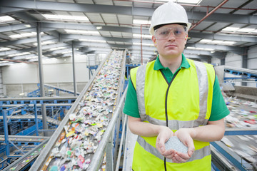 Portrait of worker holding plastic pellets in recycling plant