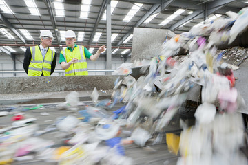 Businessman and worker talking next to conveyor belt in recycling plant