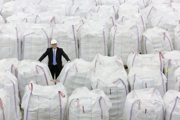 Portrait of confident businessman among large bags of recycled plastic pellets in warehouse