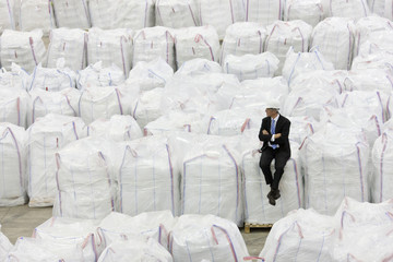 Businessman sitting on top of large bags of recycled plastic pellets in warehouse